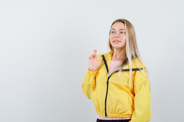 Ragazza bionda che tiene le dita incrociate in giacca gialla e sembra speranzosa.