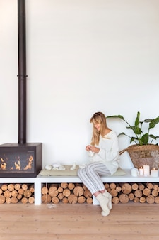 Blonde girl knits sitting on a pillow next to the fireplace in a cozy scandinavian interior