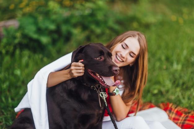 Блондинка смеется со своим другом собакой в парке
