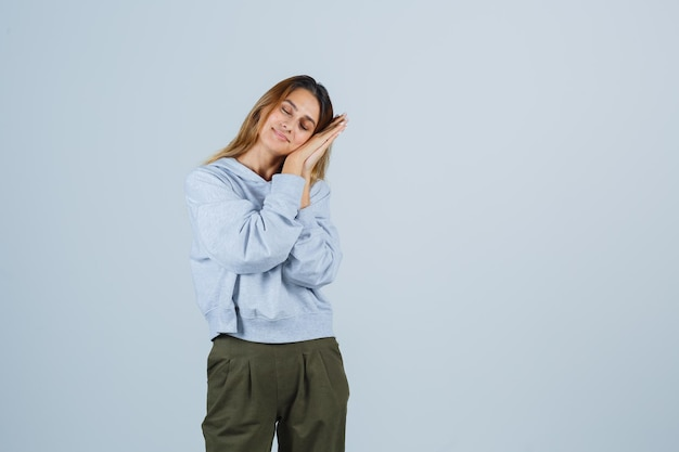 Blonde girl leaning cheek on hands, pretending to sleep in olive green blue sweatshirt and pants and looking sleepy. front view.