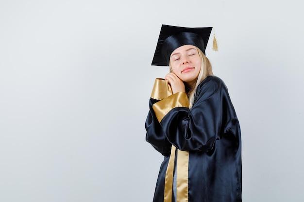 手に頬をもたれ、卒業式のガウンとキャップで目を閉じて眠そうに見えるブロンドの女の子