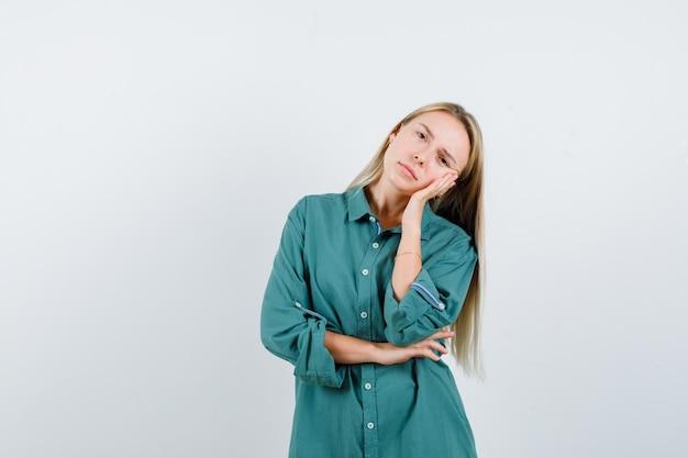 Блондинка прислонилась щекой к ладони, держась за локоть в зеленой блузке и выглядела красивой