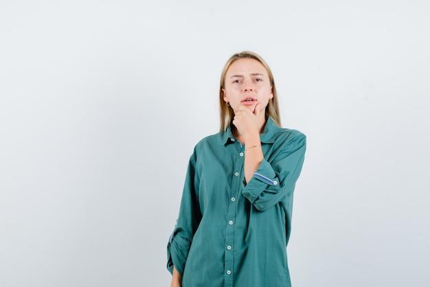 Блондинка оперлась подбородком на руку в зеленой блузке и задумчиво смотрит