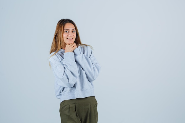 Блондинка оперлась подбородком на руки, сложила руки в оливково-зеленом синем свитере и штанах и выглядела счастливой. передний план.