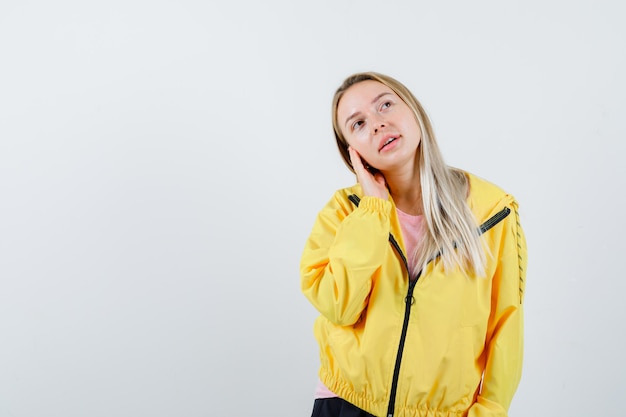 黄色のジャケットに頭をもたれ、夢のように見えるブロンドの女の子