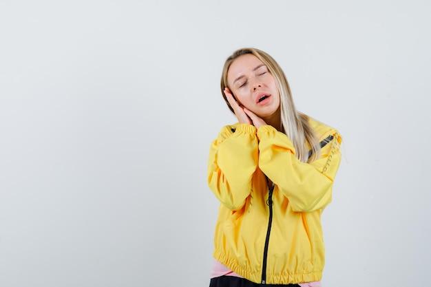 Tシャツ、ジャケットの枕として手のひらに寄りかかって、かわいく見えるブロンドの女の子