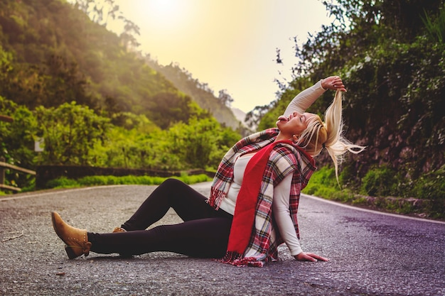 Blonde girl, living crazy, sitting in the middle of the road with her tongue out.