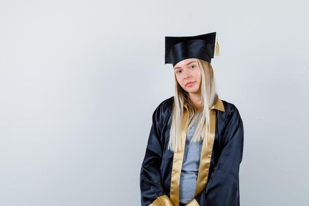 大学院の制服を着てカメラを見て、エレガントに見えるブロンドの女の子