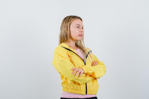 La ragazza bionda che distoglie lo sguardo ha attraversato le braccia in giacca gialla e sembra sognante,