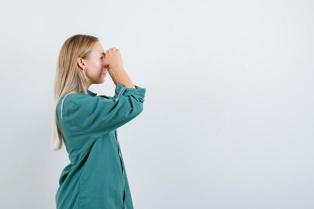 緑のブラウスで指を通して見て、焦点を当てているように見えるブロンドの女の子。