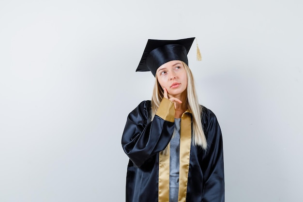 Блондинка смотрит вверх, позирует в униформе выпускника и выглядит задумчивой.