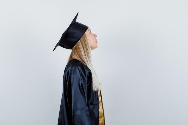 Ragazza bionda che guarda verso l'alto in uniforme laureata e sembra pensierosa.