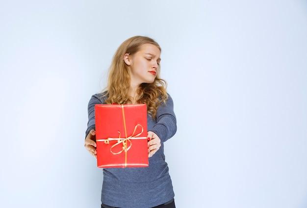 ブロンドの女の子は不満に見え、赤いギフトボックスを返します。