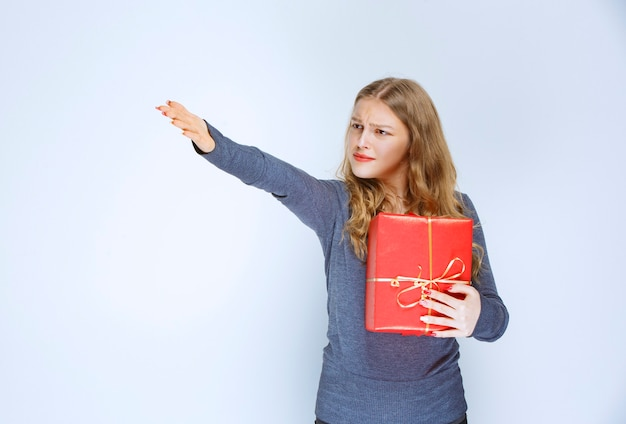 Blonde girl looks dissatisfied and returning her red gift box.