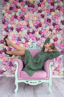 Blonde girl lying on the chair against a floral background with pleasure and happy view