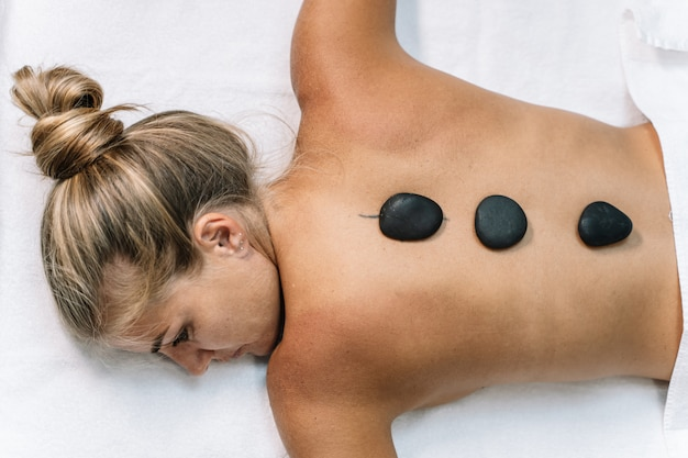 Blonde girl lying on a white towel with black stones on her back