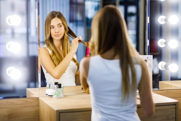 금발 소녀는 거울 앞에서 컬링 아이언의 도움으로 머리에 컬을 만듭니다