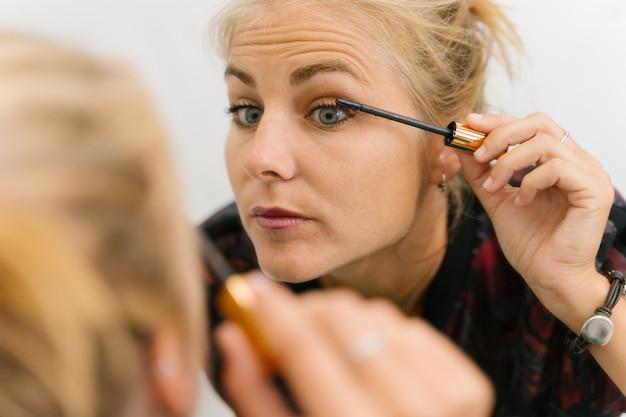 Блондинка делает макияж в тушь