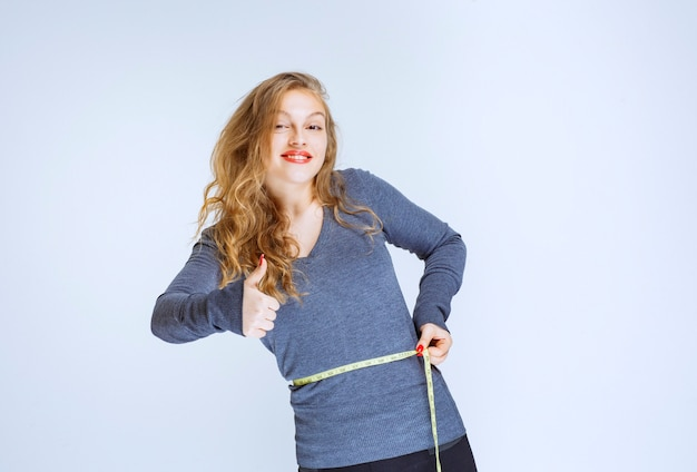 Blonde girl measuring her waist size with a tape and feeling successful.