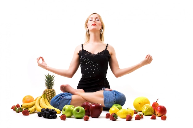 Blonde girl meditating surrounded by fruits