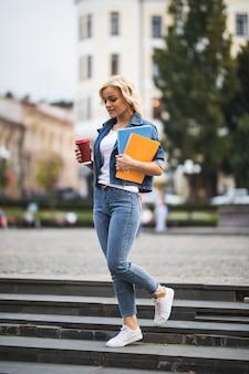 Modello di ragazza bionda sta andando alle lezioni di lavoro attraverso il citycentre tenendo il computer del caffè notebook tra le mani al mattino