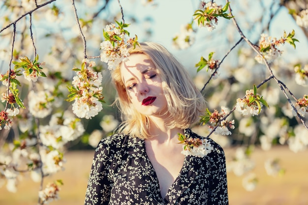 日没の田舎で咲く木の近くのブロンドの女の子