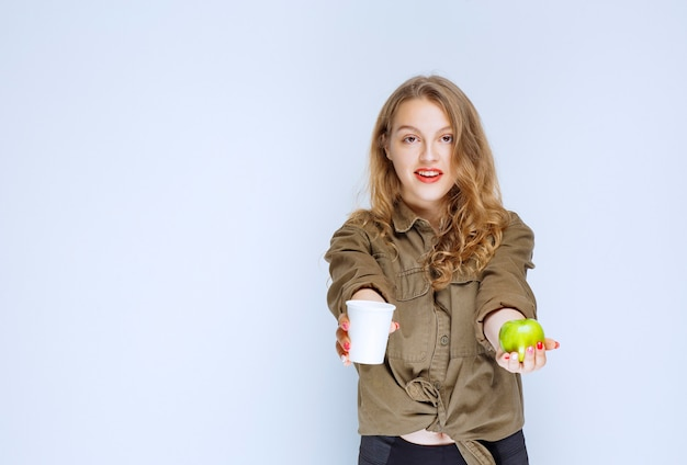 Блондинка предлагает чашку воды и зеленое яблоко.