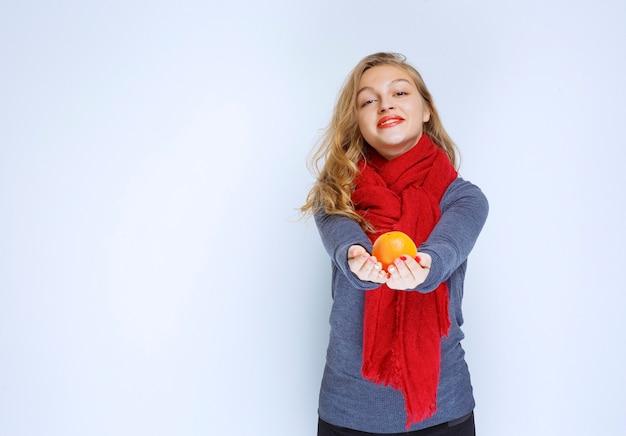 Блондинка предлагает апельсиновый плод.
