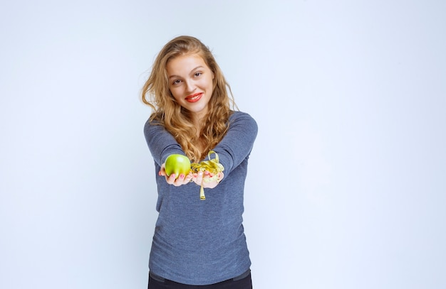 Blonde girl offering a tape and a green apple.