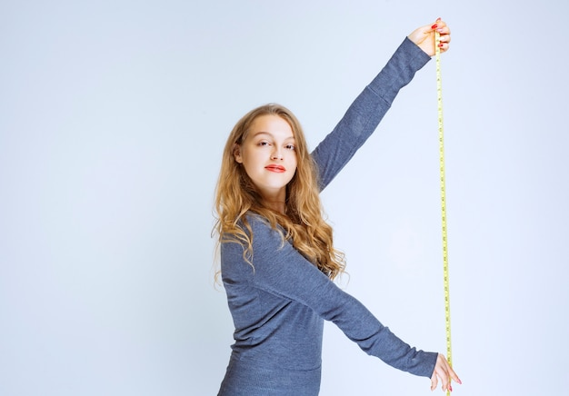 Blonde girl opening the measuring tape and showing the result.