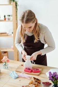 Blonde girl packing handmade soap bar on wooden board while making gifts for friends in workshop or studio