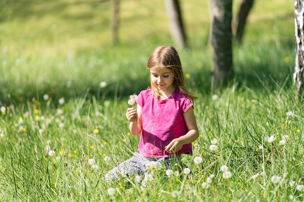Blonde girl picking flowers dandelion blowing sitting on the green grass in the field