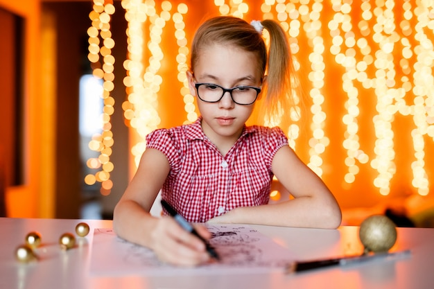 Blonde girl in the pink dress and big black glasses drawing santa claus. christmas theme