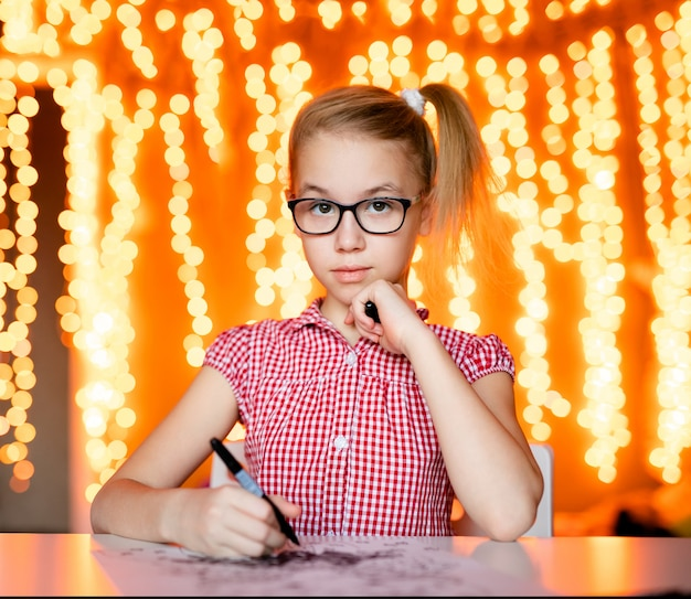 Blonde girl in the pink dress and big black glasses drawing santa claus. new year theme