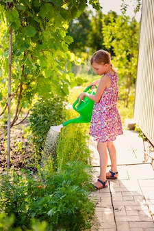 Blonde girl in pink dress watering flowers with green watering-can in the garden.