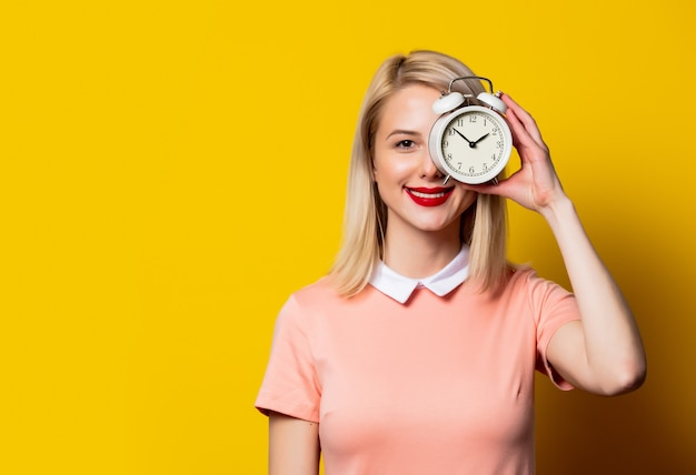 Blonde girl in pink dress with alarm clock on yellow space