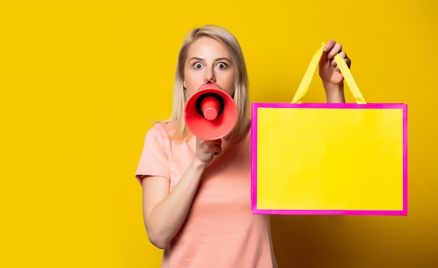 Blonde girl in pink dress with shopping bags and megaphone