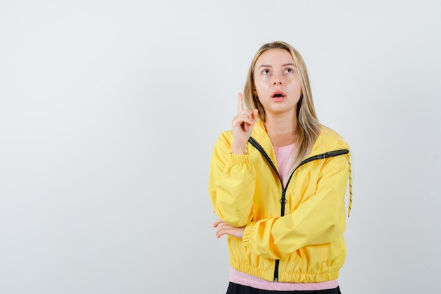 Blonde girl in pink t-shirt and yellow jacket raising index finger in eureka gesture while holding hand on elbow and looking pensive
