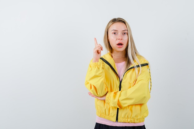 Blonde girl in pink t-shirt and yellow jacket raising index finger in eureka gesture while holding hand on elbow and looking sensible
