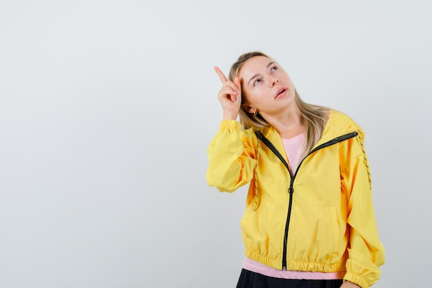 Ragazza bionda in maglietta rosa e giacca gialla che alza il dito indice sopra la testa nel gesto di eureka e sembra pensierosa