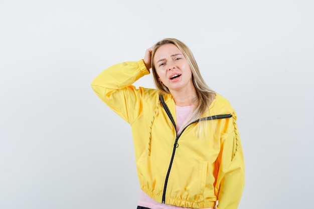 Blonde girl in pink t-shirt and yellow jacket scratching head and looking annoyed
