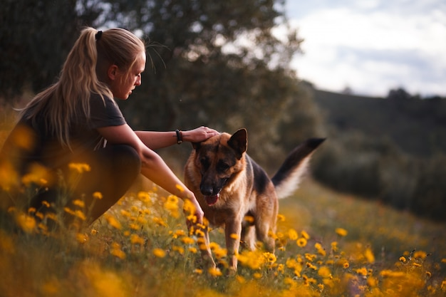 Blonde girl playing with german shepherd dog in a field of yellow flowers