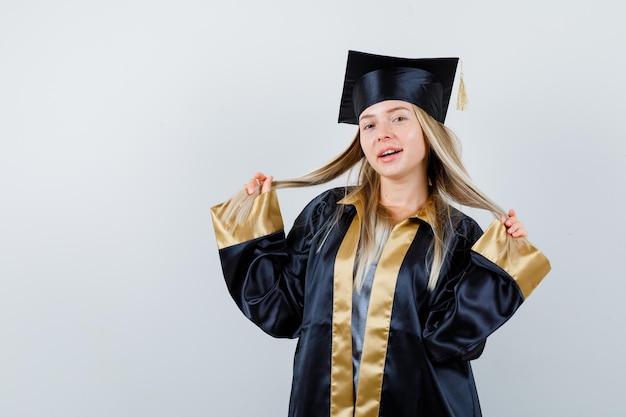 Ragazza bionda che gioca con i capelli in abito da laurea e berretto e sembra carina