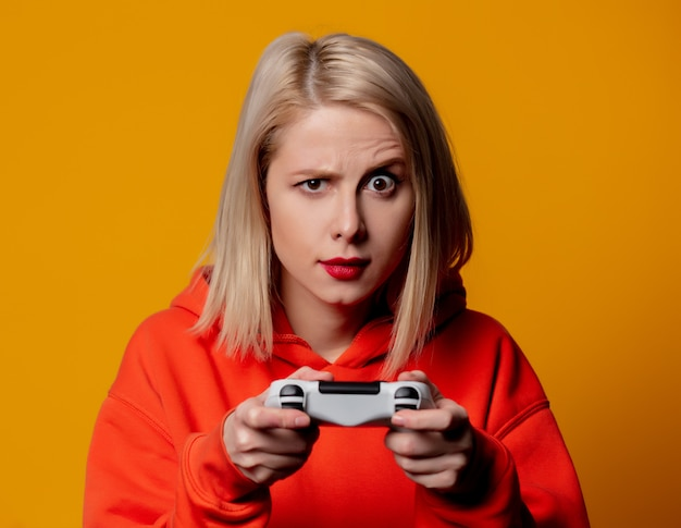 Blonde girl plays with a joystick