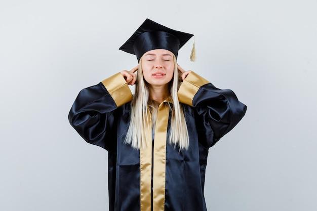 人差し指で耳をふさいで、卒業式のガウンとキャップで目を閉じて、イライラしているブロンドの女の子。
