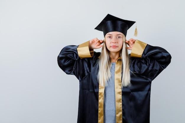 Ragazza bionda che tappa le orecchie con l'indice in abito da laurea e berretto e sembra seria