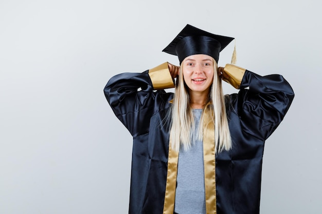 人差し指で耳をふさいで、卒業式のガウンとキャップで微笑んで、幸せそうに見えるブロンドの女の子。