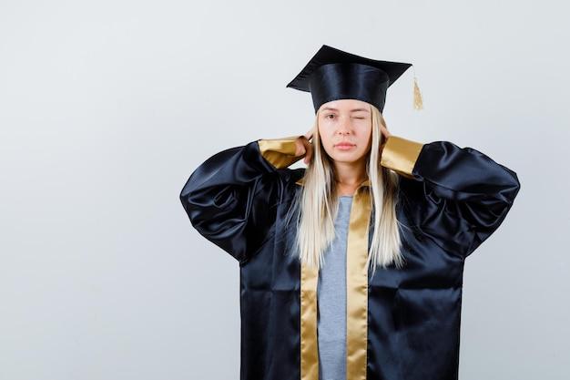 검지 손가락으로 귀를 막고 졸업 가운과 모자에 윙크하고 즐겁게 보는 금발 소녀