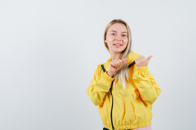 Tシャツ、ジャケット、陽気に見える親指で脇を指しているブロンドの女の子