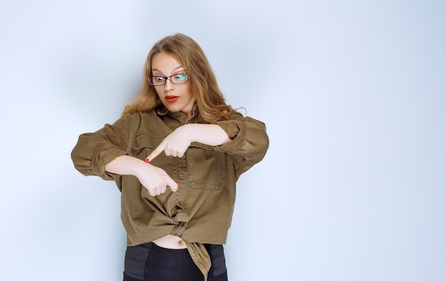 Blonde girl pointing at her watch and checking time.